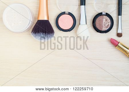 Woman earth tone cosmetics  (make up) -  brush on, lipstick, powder, brush on wood background. Top view with space for text.
