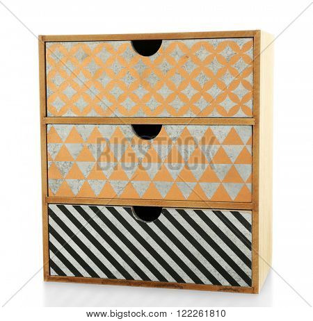 Mini handmade chest of drawers on wooden table background
