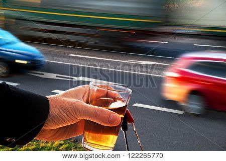 drinker with glass of alcohol by the road with cars