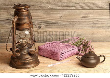 Kerosene lamp tea pot flowers and bag on wooden background