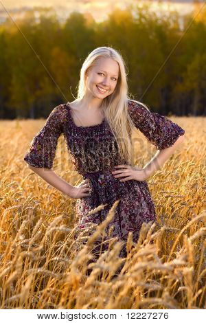 beautiful blonde woman in dress smiling at the wheat field