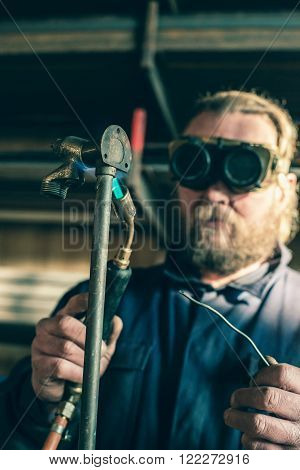 Man with safety goggles soldering iron pipe