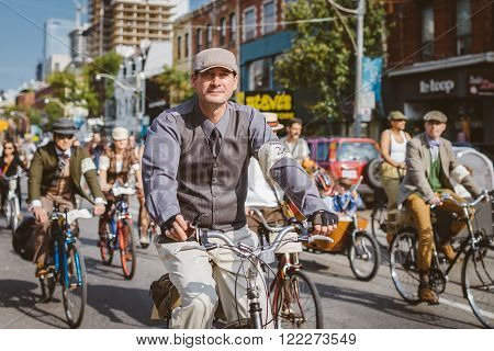 Toronto, Canada - September 20, 2014: Unidentified participants of Tweed Ride Toronto in vintage style clothes riding on their bicycles. This event is dedicated to the style of old England