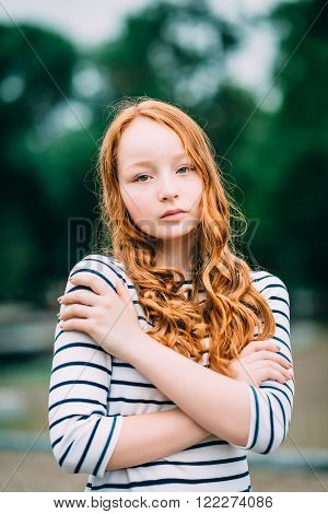 Lovely red-haired girl hugging herself and looking at camera. Beautiful young woman with red hair and green eyes in summer park. Sad teenage girl feeling herself lonely. Solitude loneliness concept