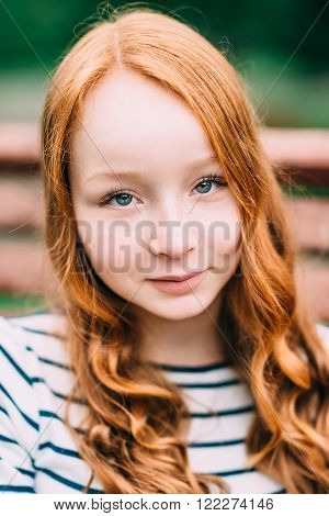 Close-up portrait of pretty smiling girl with long curly red hair in summer park. Outdoor portrait of a red-haired teenage girl. Adorable young redhead longhaired woman