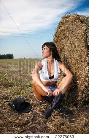 Sexy brunette sitting near a straw bale.