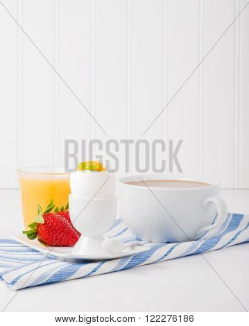 Single soft boiled egg with fresh strawberries coffee and orange juice.
