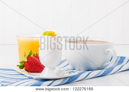 Soft boiled egg served with fresh fuit coffee and orange juice.