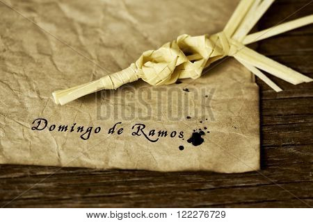 a traditional spanish braided palm to be blessed on Palm Sunday and the text Domingo de Ramos, Palm Sunday in spanish written with ink in a yellowish paper, placed on a rustic wooden surface