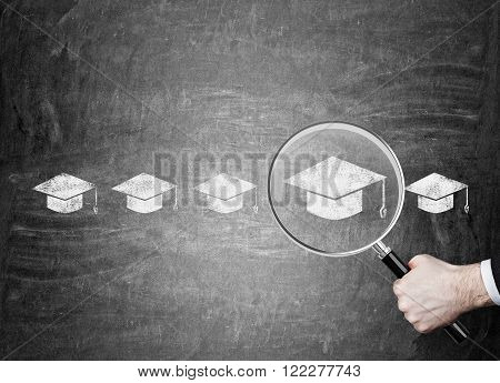 Hand holding magnifier over red picture of academic hat in row of hats. Chalk board background. Concept of choice.