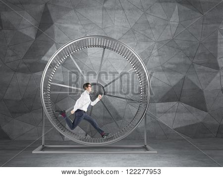 Businessman running in spinning wheel. Grey geometric background. Concept of hard work.