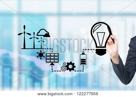 Hand drawing symbols of alternative energy sources. Blurred office background. Concept of clean environment.