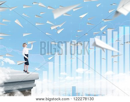 Businesswoman standing on roof throwing paper plane city view planes flying around. Blue sky and bar charts at background. Concept of starting new project.