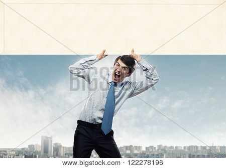 Emotional businessman lifting empty banner above his head