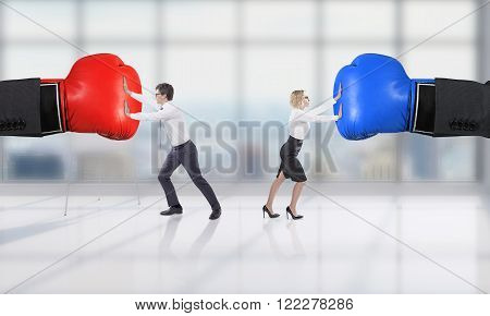 Two hands in boxer gloves businessman and businesswoman pushing them in different directions. Concept of rivalry.