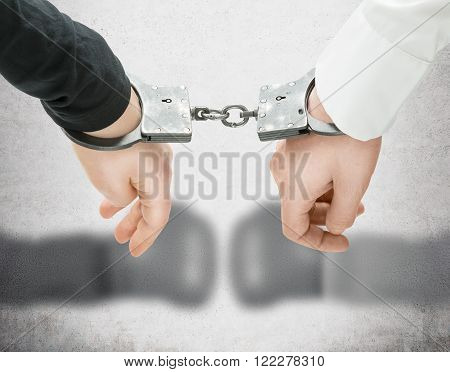 Hands of two men fixed in handcuffs. Close up. Blurred hands in boxer gloves at background. Concept of accessory of crime.