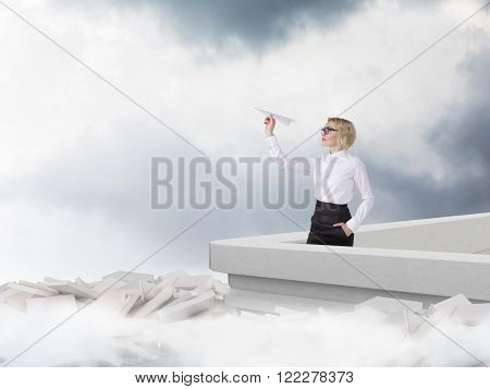 Businesswoman with paper plane on roof white book scattered at bottom sky and clouds at background. Concept of new start.