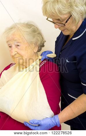 Nurse putting a senior ladies broken arm in a sling, showing obvious pain in ladies pale face