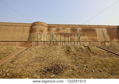 the red brickwork of bathinda fort in the punjab under a blue sky in springtime
