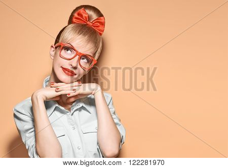 Beauty fashion woman in stylish glasses thinking, idea. Attractive happy blonde hipster girl smiling, emotional. Confidence, success, Pinup hairstyle. Unusual playful, expression nerd.Vintage, vanilla