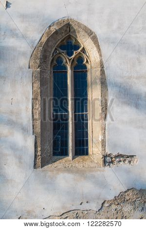 Original gothic window with a stone frame and a glass reflecting the sky. Church of Saint Cross in Devin Bratislava Slovakia.