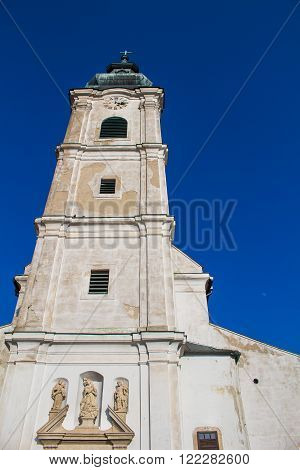 Church of Saint Cross. Old facade high tower with clock. Cross on the tower. Bright blue sky.