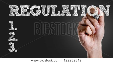 Hand writing the text: Regulation