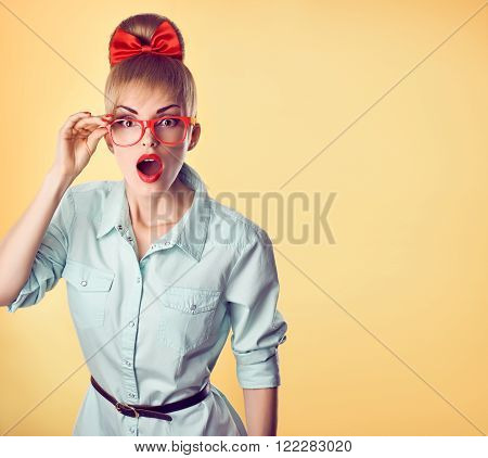 Beauty fashion nerd woman in stylish glasses surprised. Attractive pretty funny blonde girl open mouth. Confidence, success, Pinup hairstyle bow makeup. Unusual playful, expression.Vintage, on yellow