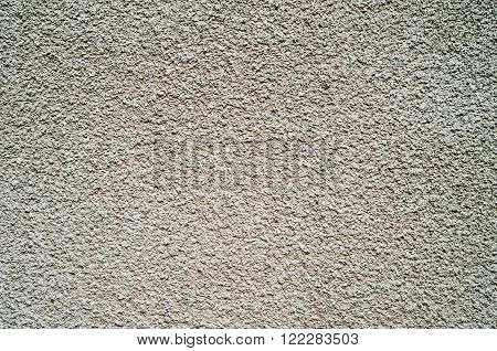Detail of gray wall closeup uneven granular cement coating for use as a background
