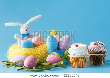Easter decoration with eggs and sweets on blue background