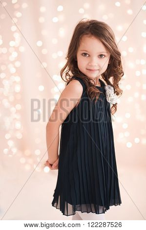 Cute baby girl 5-6 year old wearing stylish dress over lights in room. Looking at camera. Birthday party. Celebration.