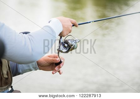 Fisherman on the river bank. Man fisherman catches a fish. Fisherman in his hand holding spinning. Fishing, spinning reel, fish, Breg rivers. - The concept of a rural getaway. Article about fishing.