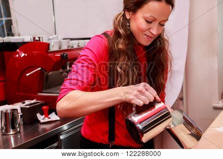 Female bartender in the workplace. Girl makes coffee using coffee machine. Coffee, cappuccino, coffee, coffee shop, the bartender - the concept of catering. Use in articles about coffee.