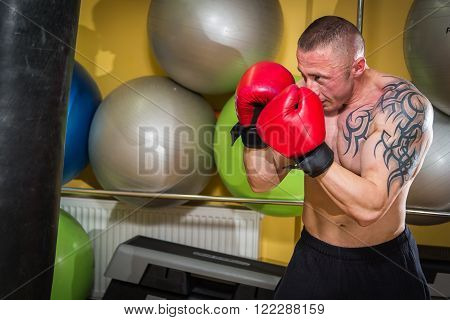 Muscular man in the gym. The man in boxing gloves, hit a punching bag, exercise.