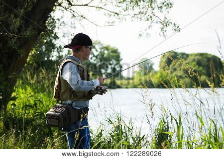 Fisherman on the river bank. Man fisherman catches a fish. Fisherman in his hand holding spinning. Fishing, spinning reel, fish, Breg rivers. - The concept of a rural getaway.