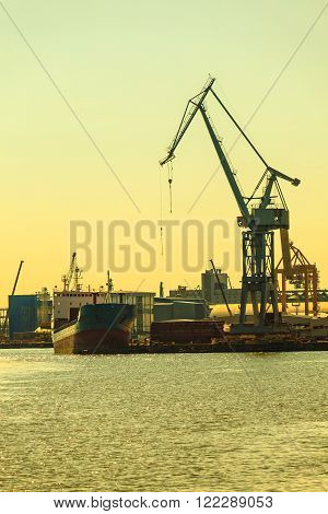Business and commerce. Heavy load dockside cranes in port, cargo container yard. Industrial scene