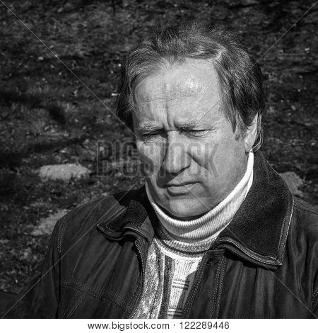 Black and white close up portrait of a mature man in deep thought.
