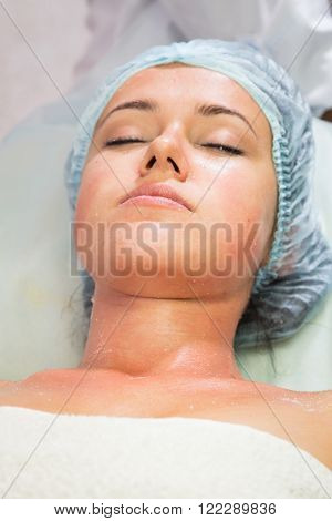 The cosmetic procedures for the face. Makeup artist applies invigorating mask on the face of the model. Beauty treatments in the spa salon. Facial Skin Care.