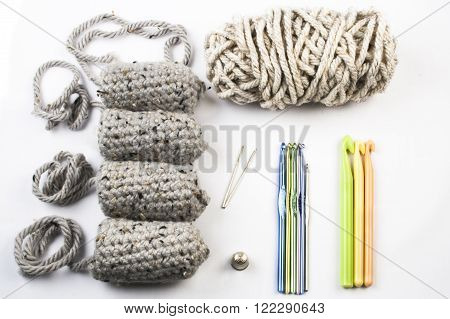 Tools for a crocheted amigurumi doll including yarn hooks sewing needles thimble and doll legs