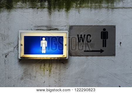lamp and signage with the sign of the men's room toilet on a old dirty wall, grunge concept with copy space