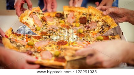Image of friends hands taking slices of pizza.Pizza with mozzarella cheese and fresh tomato.
