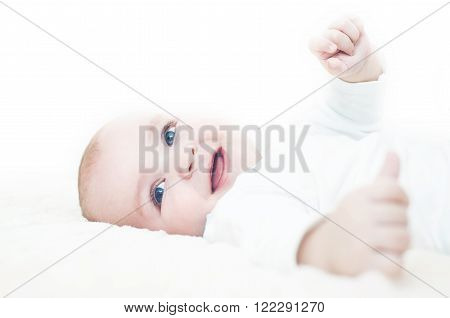 Bright closeup portrait of adorable baby.Funny laughing baby lying on back and looking over the camera with a big smile.
