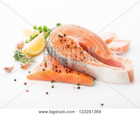 salmon raw. salmon red fish steak with herbs and lemon isolated on a white background