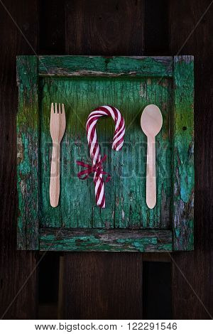 Antique rustic mint green wood background with wooden spoon and fork near candy cane up view