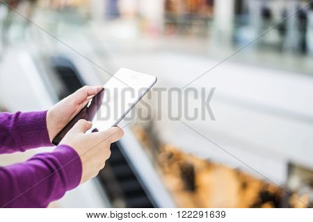 Woman using her Digital Tablet in shopping center