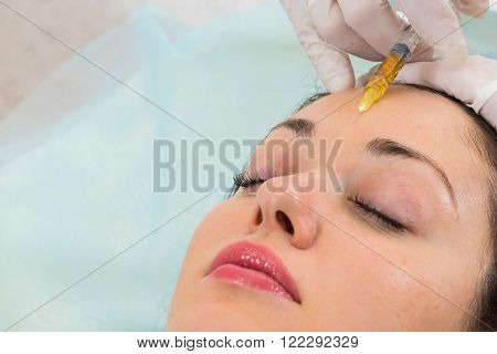 Cosmetic injection in the spa salon. Beautician makes injection into the patient's face.