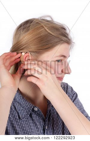 Girl inserting her hearing aid into her ear. Studio isolated on white background.