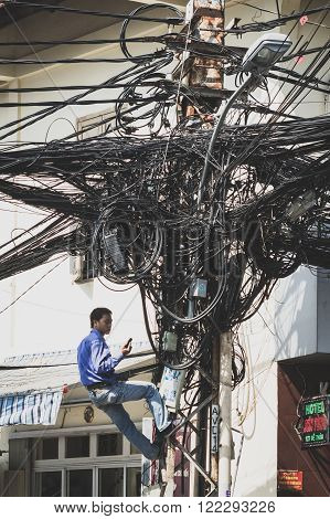 Saigon Vietnam - January 20 2014: Electrician fixing messy cables on telephone mast.