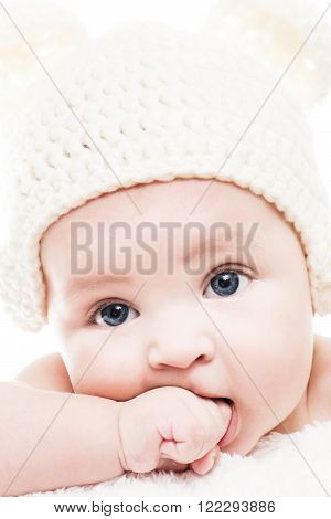 Close up head shot of a caucasian baby boy.Baby wearing a knit hat with bear ears.