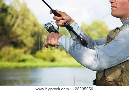 Fisherman on the river bank in sunglasses.Fisherman in his hand holding spinning. Fishing, spinning reel, fish, Breg rivers. - The concept of a rural getaway. Article about fishing.